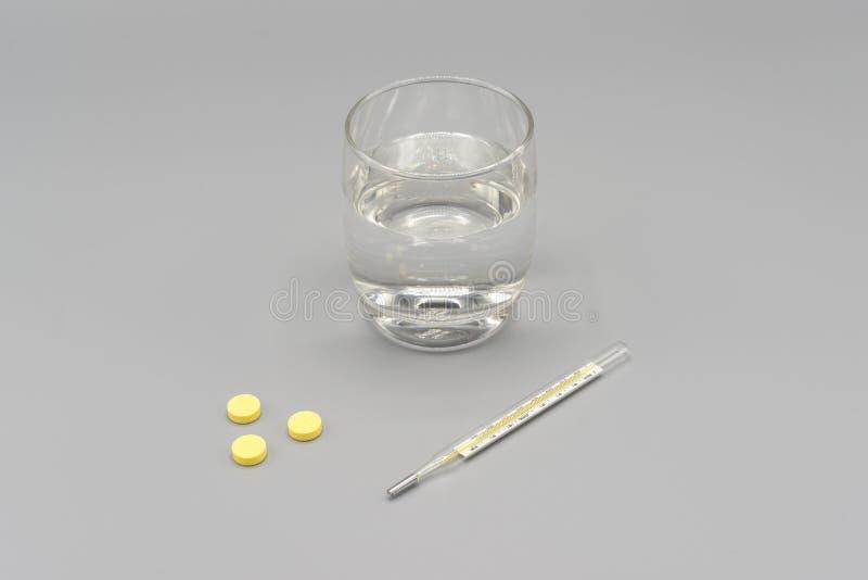 Κίτρινα χάπια, θερμόμετρο και ποτήρι του νερού στο γκρίζο υπόβαθρο στοκ εικόνες