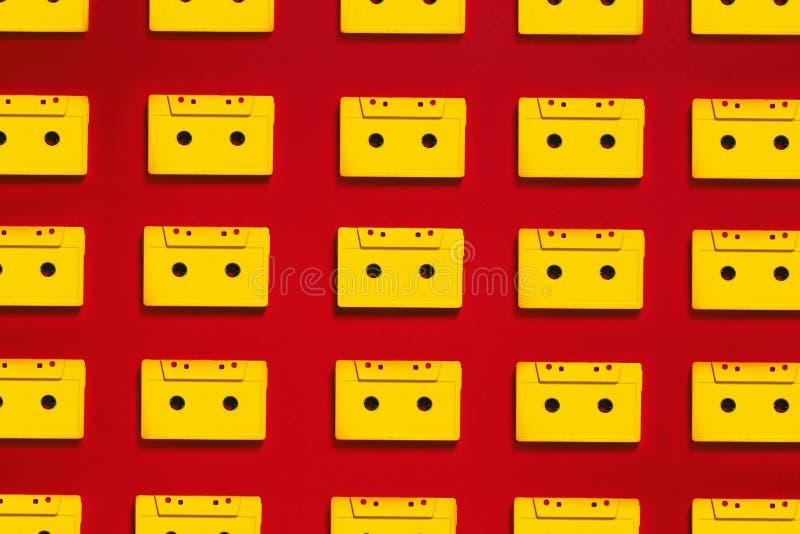 Κίτρινες ακουστικές ταινίες κασετών συλλογής στο κόκκινο υπόβαθρο, τοπ άποψη Δημιουργική έννοια της αναδρομικής τεχνολογίας στοκ φωτογραφίες με δικαίωμα ελεύθερης χρήσης
