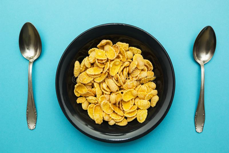 Κίτρινες νιφάδες καλαμποκιού σε ένα μαύρο πιάτο σε ένα μπλε υπόβαθρο στοκ εικόνα με δικαίωμα ελεύθερης χρήσης