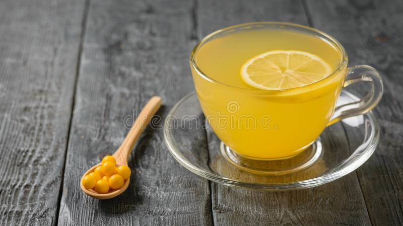 Κίτρινες ταμπλέτες σε ένα ξύλινο κουτάλι και ένα ποτό της πιπερόριζας και εσπεριδοειδή σε έναν μαύρο πίνακα στοκ φωτογραφία με δικαίωμα ελεύθερης χρήσης