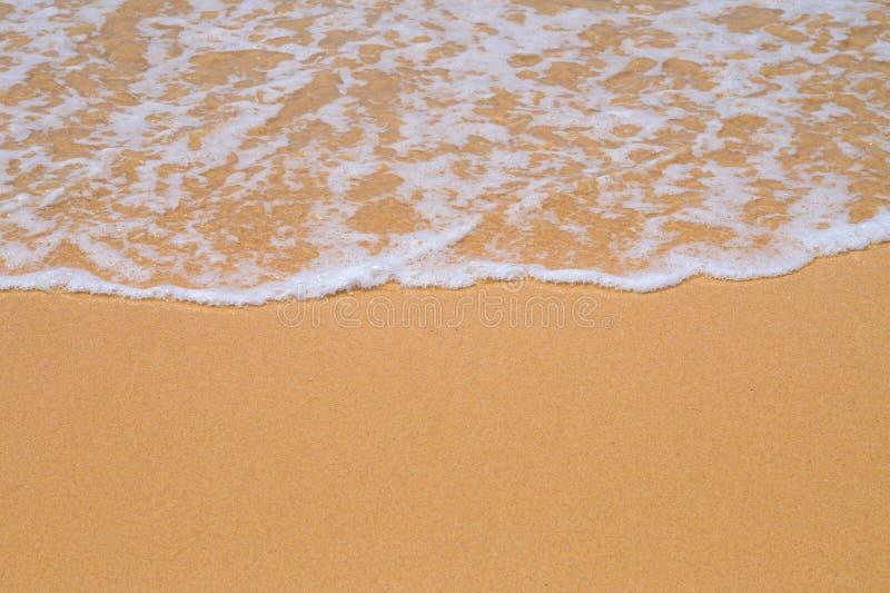 Κίτρινη άμμος παραλιών που καλύπτεται με τον άσπρο αφρό κυμάτων στοκ φωτογραφία