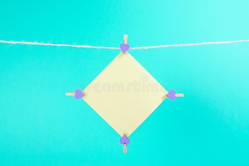 Κίτρινη αυτοκόλλητη ετικέττα στη σκοινί για άπλωμα με τα clothespins που απομονώνονται στο μπλε υπόβαθρο στοκ φωτογραφία