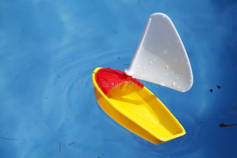 Κίτρινη βάρκα παιχνιδιών στη λίμνη των παιδιών στοκ εικόνες