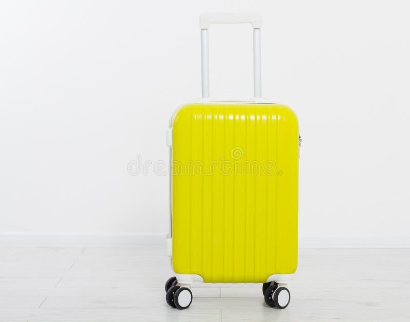 Κίτρινη βαλίτσα στο άσπρο υπόβαθρο οικογενειακό καλές διακοπές καλοκαίρι σας Το ταξίδι ή τοποθετεί σε σάκκο Χλεύη επάνω διάστημα  στοκ φωτογραφία με δικαίωμα ελεύθερης χρήσης