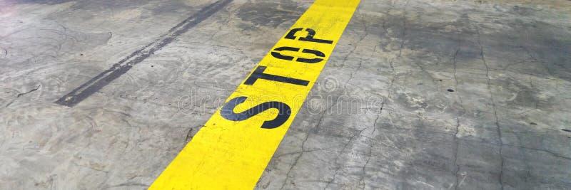 Κίτρινη γραμμή με τη ΣΤΑΣΗ στον υπόγειο υπαίθριο σταθμό αυτοκινήτων στοκ εικόνα