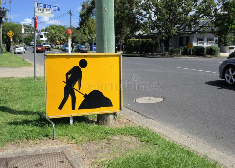 Κίτρινη επιτροπή σημαδιών του εργαζόμενου ατόμου για να προειδοποιήσει τους οδηγούς στοκ εικόνες