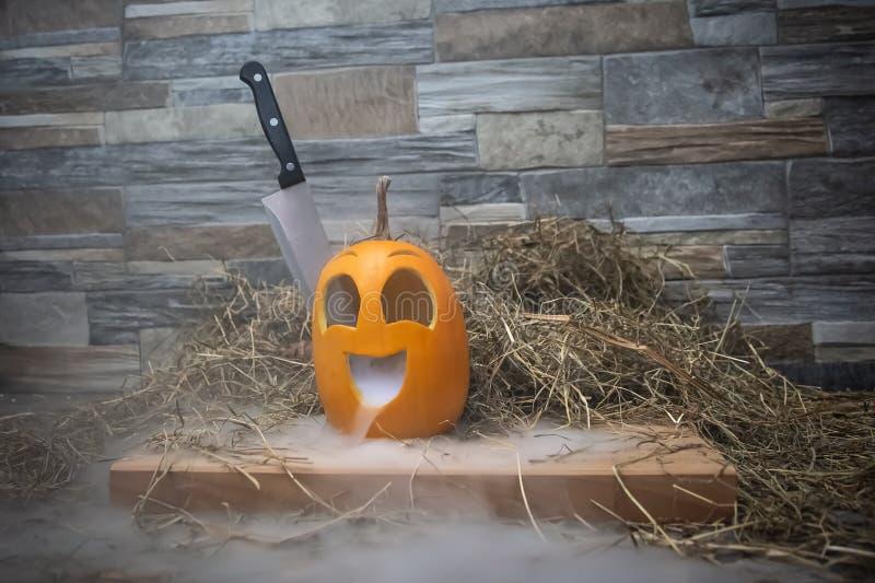 Κίτρινη και αστεία κολοκύθα με μαχαίρι στο κεφάλι και καπνό ή ατμό από το στόμα του Στέκεται σε ξύλινη βάση ενάντια σε στοκ φωτογραφίες με δικαίωμα ελεύθερης χρήσης