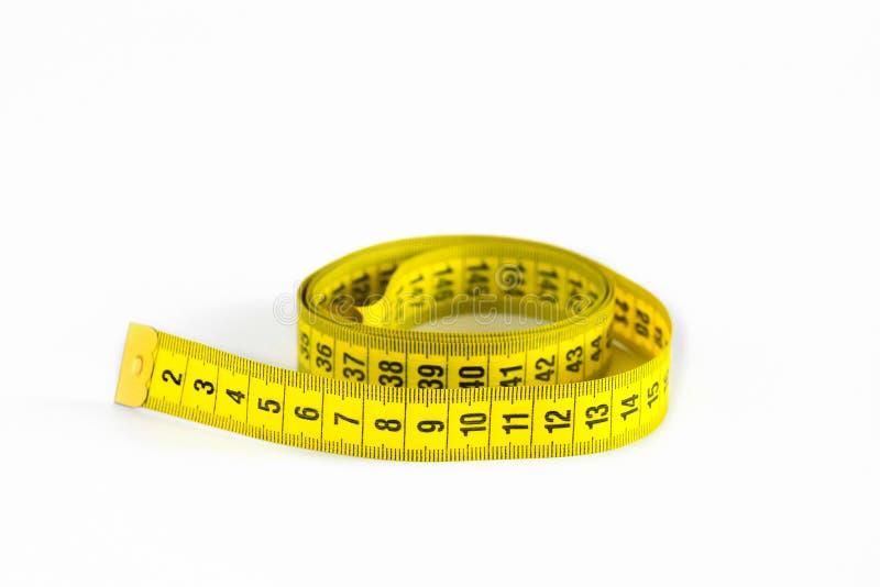 Κίτρινη μετρώντας ταινία στα εκατοστόμετρα που απομονώνονται στο άσπρο υπόβαθρο στοκ εικόνες με δικαίωμα ελεύθερης χρήσης