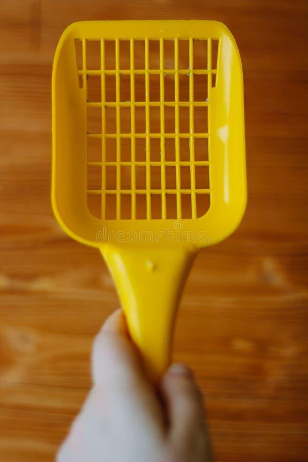 Κίτρινη πλαστική σέσουλα για τον καθαρισμό των απορριμάτων κατοικίδιων ζώων πέρα από το ξύλινο υπόβαθρο στοκ εικόνα με δικαίωμα ελεύθερης χρήσης