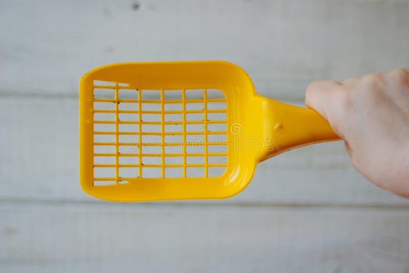 Κίτρινη πλαστική σέσουλα για τον καθαρισμό των απορριμάτων κατοικίδιων ζώων πέρα από το ξύλινο υπόβαθρο στοκ φωτογραφία με δικαίωμα ελεύθερης χρήσης