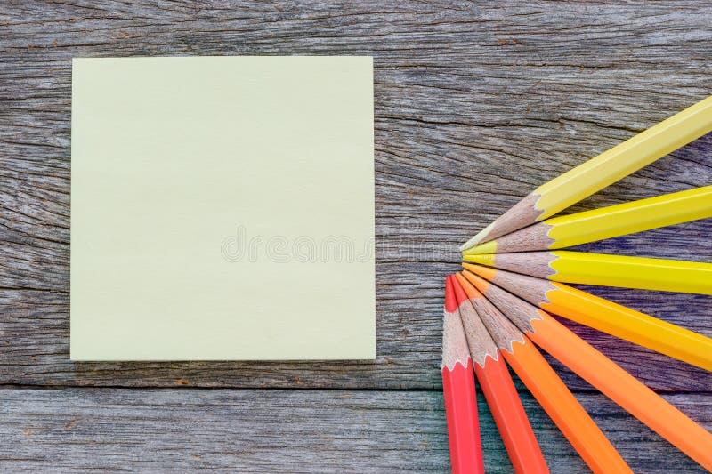 Κίτρινη σημείωση meno και χρωματισμένα μολύβια στο ξύλινο υπόβαθρο στοκ φωτογραφία με δικαίωμα ελεύθερης χρήσης