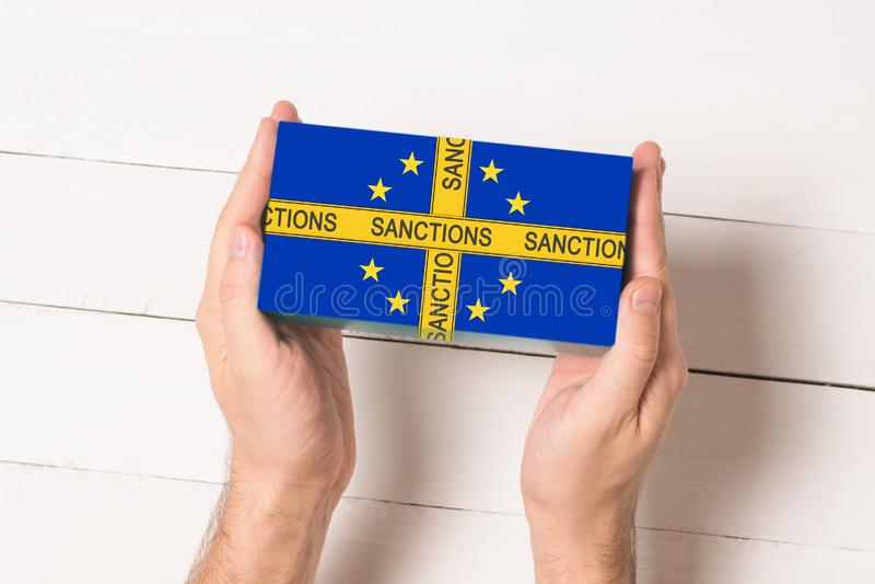 Κίτρινη ταινία με τις κυρώσεις επιγραφής στο κιβώτιο με τη σημαία της Ευρωπαϊκής Ένωσης στα αρσενικά χέρια Άσπρος πίνακας τοπ άπο στοκ εικόνες
