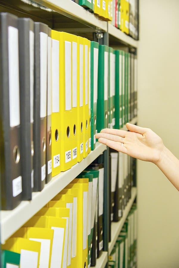 Κίτρινοι και πράσινοι φάκελλοι αρχείων στο αρχείο και το ανθρώπινο χέρι στοκ φωτογραφίες με δικαίωμα ελεύθερης χρήσης