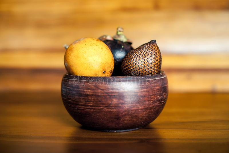 Κίτρινοι λωτοί, mangosteen και salak στο ξύλινο κύπελλο Μίγμα των εξωτικών νωπών καρπών από το Μπαλί, Ινδονησία στοκ εικόνα