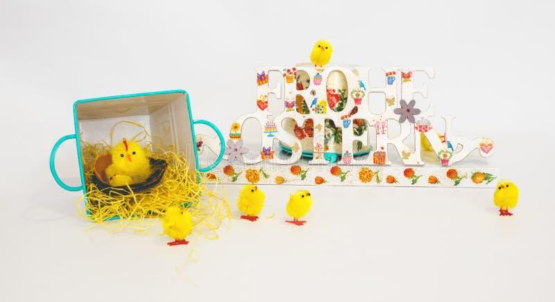 Κίτρινοι νεοσσοί γύρω από τα χρωματισμένα συγχαρητήρια ευτυχές Πάσχα στα γερμανικά στο λευκό Ντεκόρ για το σπίτι και τον κήπο στοκ εικόνες