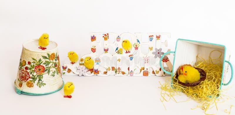 Κίτρινοι νεοσσοί παιχνιδιών γύρω από τα χρωματισμένα συγχαρητήρια ευτυχές Πάσχα στα γερμανικά στο άσπρο υπόβαθρο στοκ εικόνες με δικαίωμα ελεύθερης χρήσης