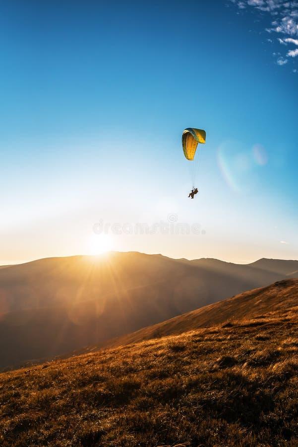 Κίτρινος αλεξιπτωτιστής που πετάει στον ουρανό το ηλιοβασίλεμα στοκ εικόνες