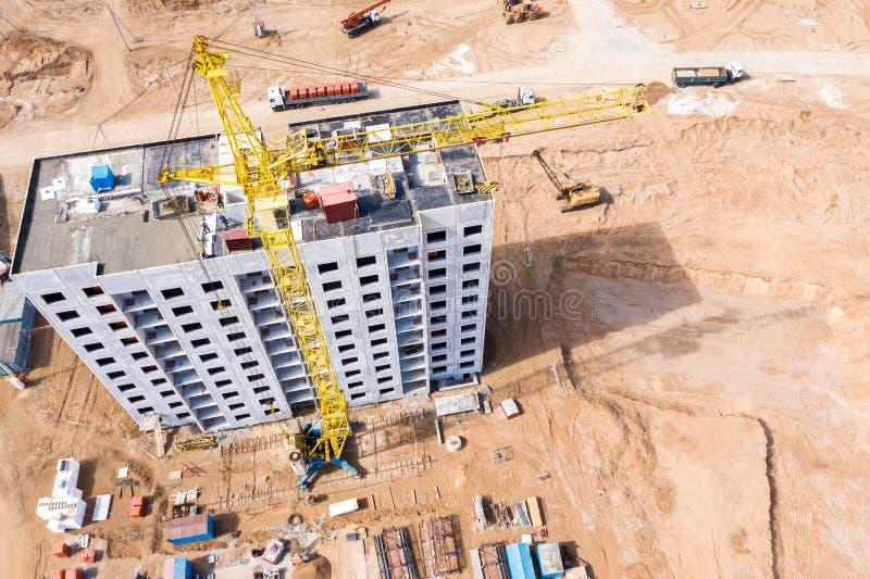 Κίτρινος γερανός πύργων που στέκεται κοντά στη νέα πολυκατοικία κάτω από την κατασκευή ( στοκ εικόνα με δικαίωμα ελεύθερης χρήσης