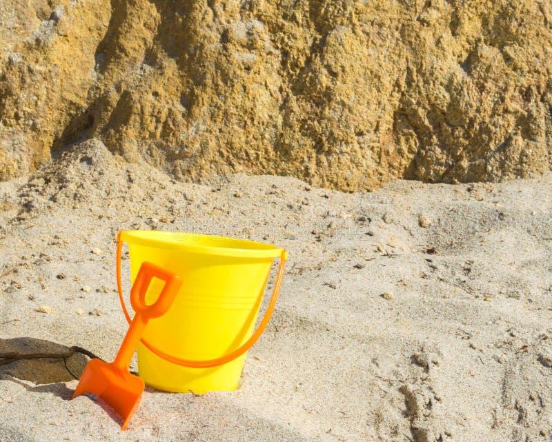 Κίτρινος κάδος άμμου με το πορτοκαλί φτυάρι στην παραλία κοντά σε έναν απότομο τοίχο βράχου στοκ φωτογραφία
