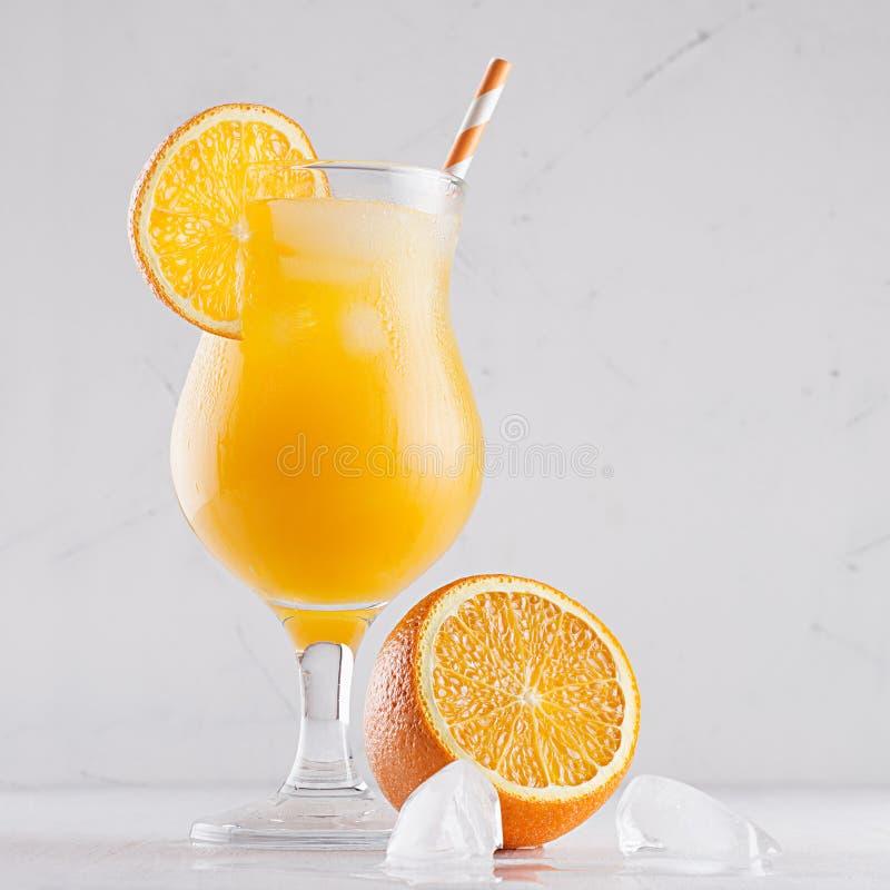 Κίτρινος κρύος χυμός με τους κύβους πάγου, το άχυρο και τα μισά πορτοκάλια στο μαλακό άσπρο υπόβαθρο επιμεταλλωτών, τετράγωνο, κι στοκ φωτογραφία