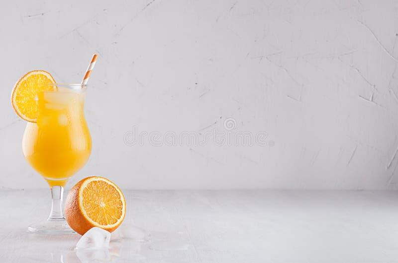 Κίτρινος κρύος χυμός με τους κύβους πάγου, το άχυρο και τα μισά πορτοκάλια στο μαλακό άσπρο υπόβαθρο επιμεταλλωτών στοκ φωτογραφία