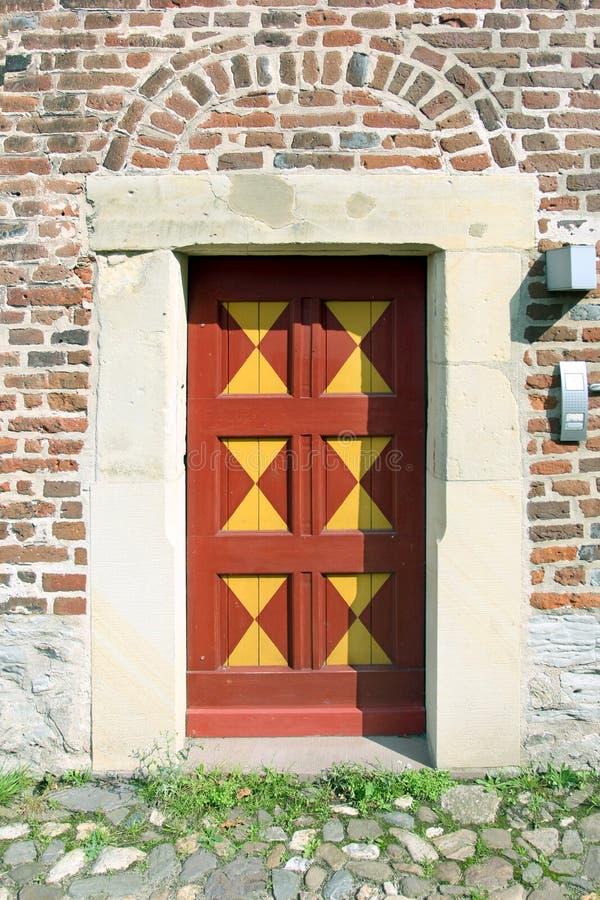 Κίτρινος-κόκκινη τετραγωνική πόρτα στον παλαιό λιθοστρωμένο τοίχο στοκ φωτογραφία με δικαίωμα ελεύθερης χρήσης