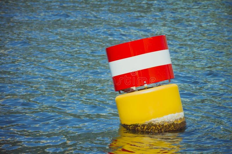 Κίτρινος κόκκινος και άσπρος πλοήγησης επιπλέων σημαντήρας χάλυβα στο blu στοκ εικόνα με δικαίωμα ελεύθερης χρήσης