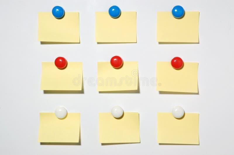 Κίτρινος μετα αυτό κουμπί σημειώσεων και μαγνητών στο whiteboard στοκ εικόνες