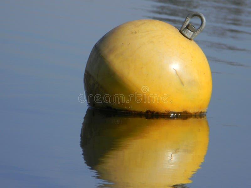 Κίτρινος σημαντήρας νερού που επιπλέει στην ήρεμη λίμνη στοκ εικόνα με δικαίωμα ελεύθερης χρήσης