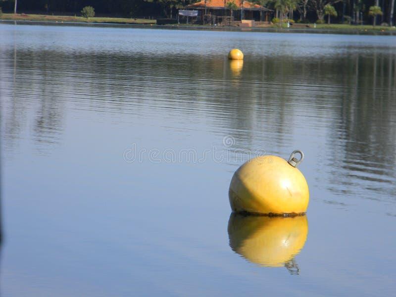 Κίτρινος σημαντήρας νερού που επιπλέει στην ήρεμη λίμνη στοκ εικόνες με δικαίωμα ελεύθερης χρήσης