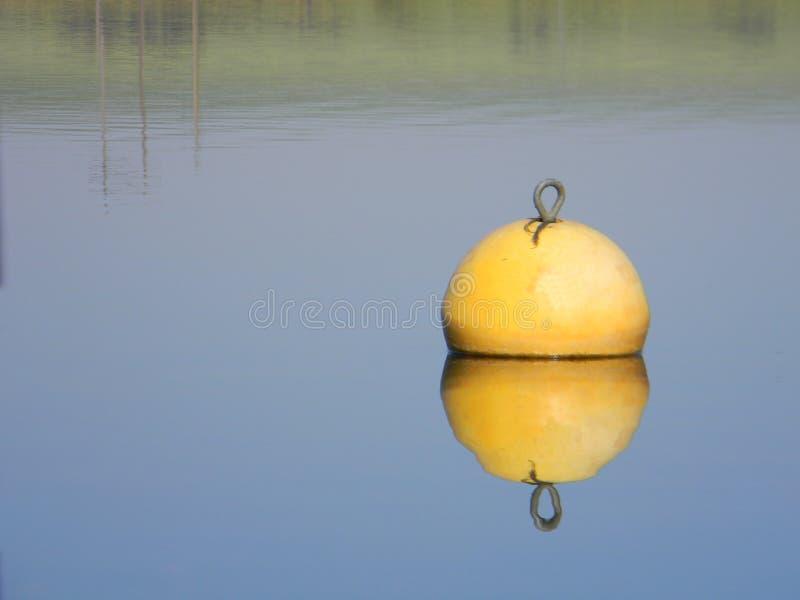 Κίτρινος σημαντήρας νερού που επιπλέει στην ήρεμη λίμνη στοκ φωτογραφίες