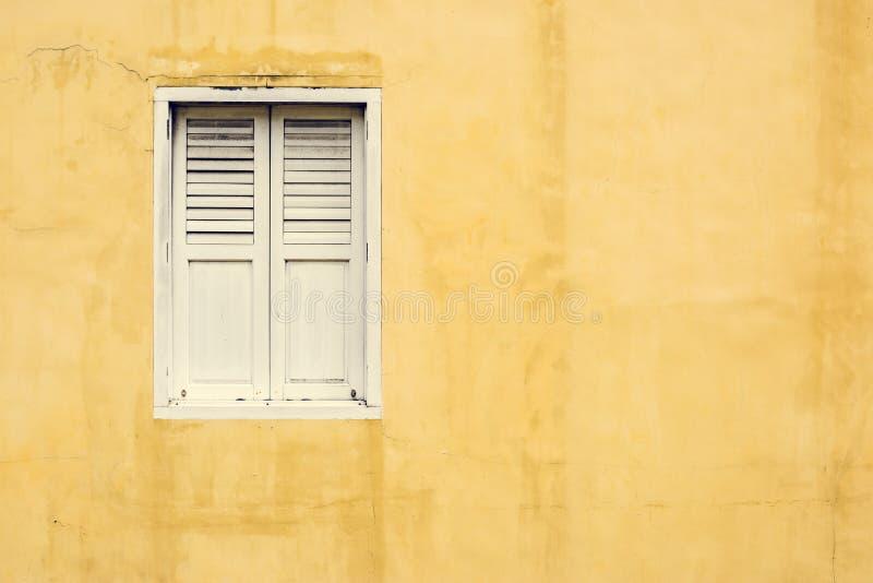 Κίτρινος τοίχος και ένα άσπρο παράθυρο στοκ εικόνες με δικαίωμα ελεύθερης χρήσης