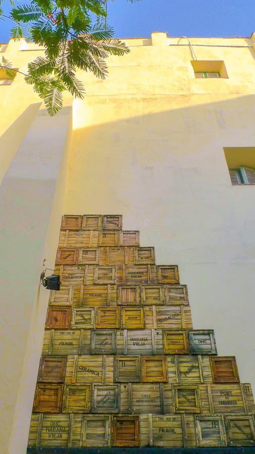 Κίτρινος τοίχος που διακοσμείται με τα ξύλινα κλουβιά φορτίου στοκ εικόνα