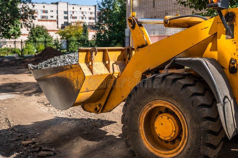 Κίτρινος φορτωτής τον κάδο που φορτώνεται με από το αμμοχάλικο στο εργοτάξιο οικοδομής στοκ εικόνα