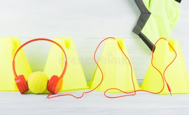 Κίτρινος φράκτης κώνων στην γκρίζα μπλούζα υποβάθρου και αθλητισμού, πίσω από τη σφαίρα αντισφαίρισης που φορά τα κόκκινα ακουστι στοκ εικόνα με δικαίωμα ελεύθερης χρήσης