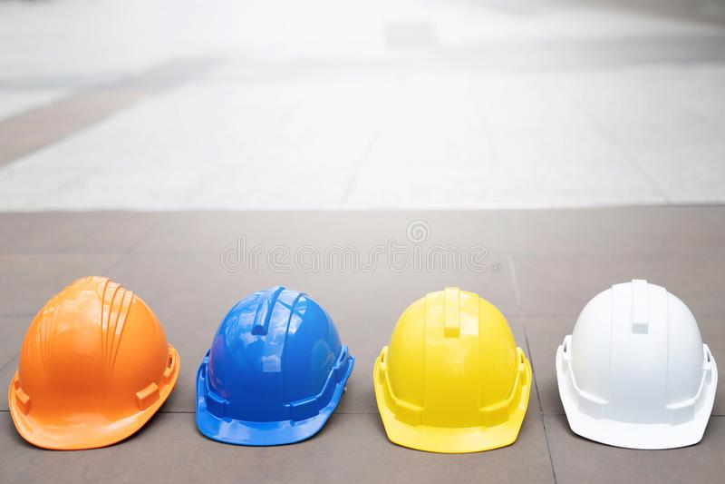 Κίτρινο, άσπρο, μπλε σκληρό καπέλο κρανών ένδυσης ασφάλειας στο πρόγραμμα στο εργοτάξιο οικοδομής στοκ εικόνες με δικαίωμα ελεύθερης χρήσης
