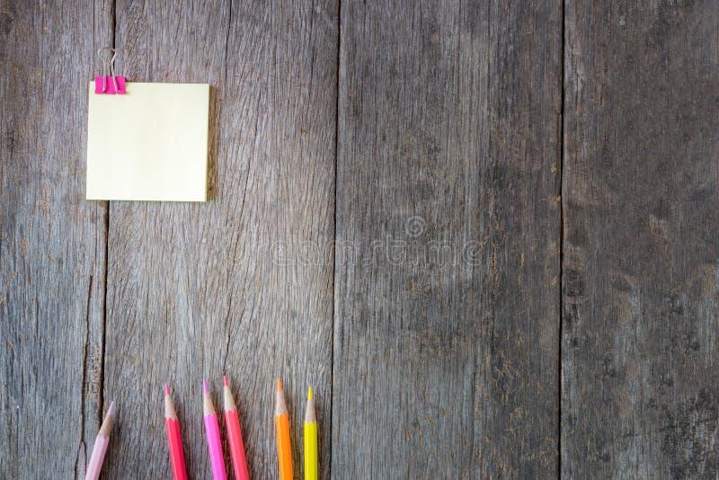 Κίτρινο έγγραφο σημειώσεων για το ξύλινο υπόβαθρο με τα χρωματισμένα μολύβια στοκ φωτογραφία