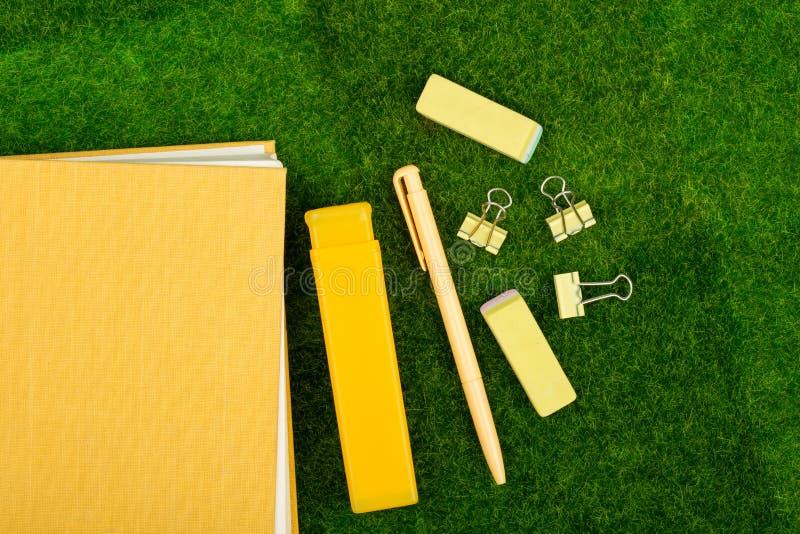 κίτρινο βιβλίο, συνδετήρας συνδέσμων και γόμες στη χλόη στοκ εικόνες