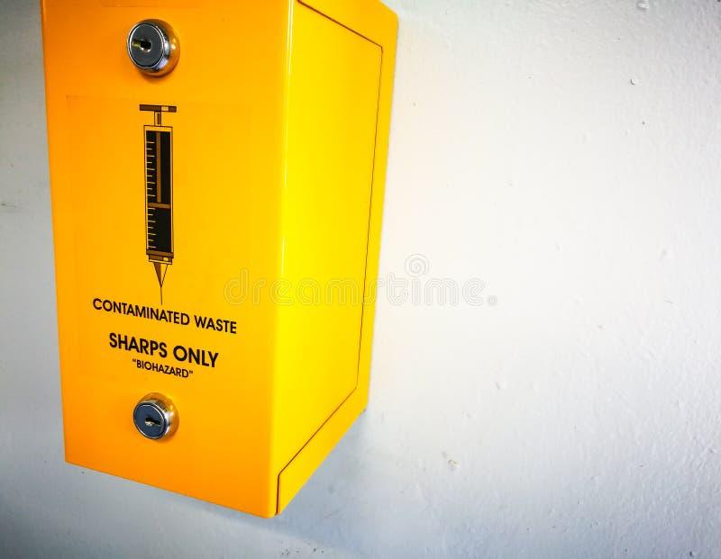 Κίτρινο δοχείο κιβωτίων στον άσπρο τοίχο για τη μολυσμένη μορφή Biohazard αποβλήτων μόνο στοκ εικόνες