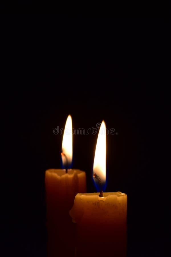 Κίτρινο ελαφρύ κάψιμο κεριών λαμπρά στο μαύρο υπόβαθρο στοκ φωτογραφίες