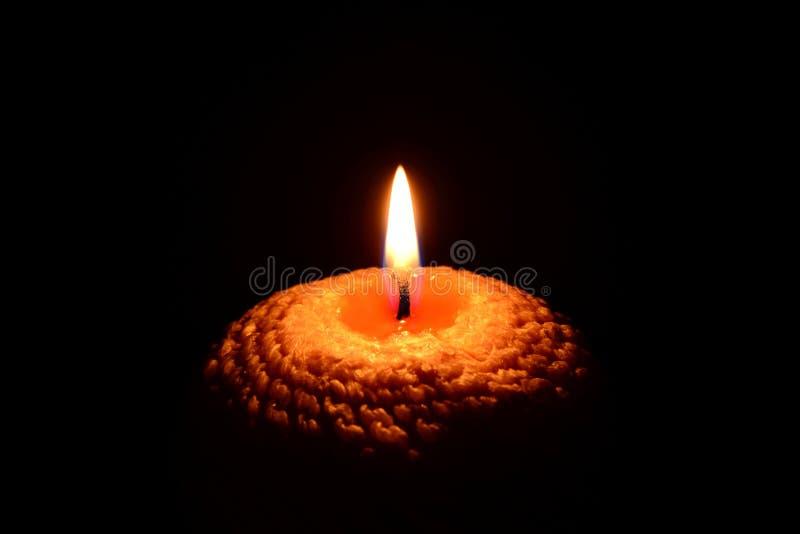 Κίτρινο κάψιμο κεριών σε ένα μαύρο υπόβαθρο στοκ εικόνα