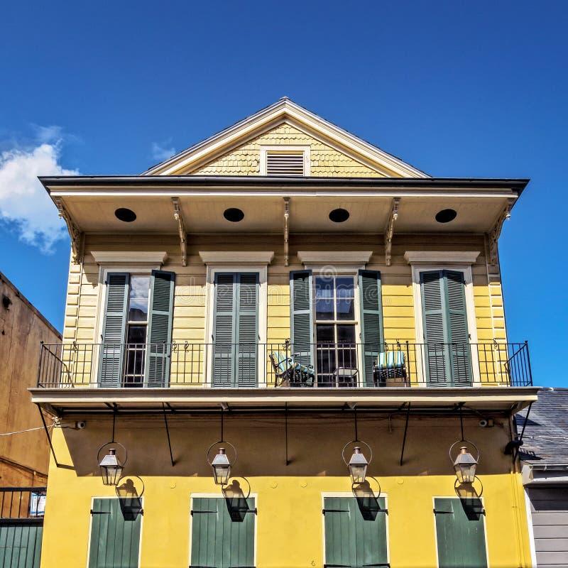 Κίτρινο κτήριο με 4 λαμπτήρες αερίου, τις πράσινα πόρτες και τα παραθυρόφυλλα Frenc στοκ εικόνες με δικαίωμα ελεύθερης χρήσης