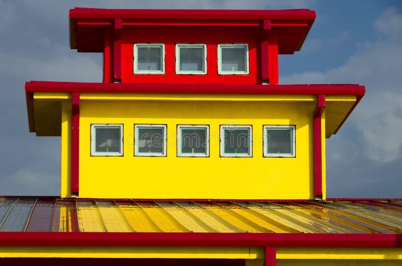 Κίτρινο κτήριο με την κόκκινη περιποίηση στοκ εικόνα