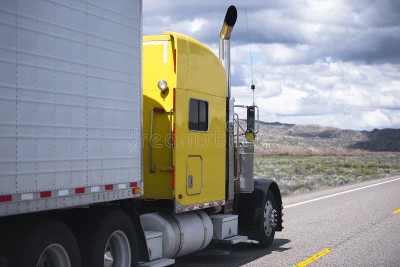 Κίτρινο κλασικό ημι φορτηγό που πηγαίνει από την επικείμενη γραμμή κυκλοφορίας δρόμου στοκ φωτογραφίες με δικαίωμα ελεύθερης χρήσης
