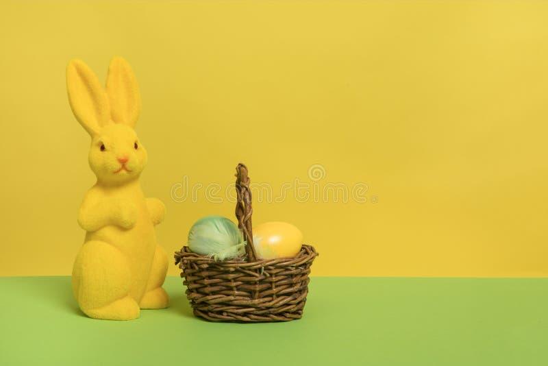Κίτρινο λαγουδάκι Πάσχας διακοσμήσεων με ένα καλάθι με τα αυγά σε ένα κίτρινο και πράσινο υπόβαθρο με το διάστημα αντιγράφων στοκ εικόνες με δικαίωμα ελεύθερης χρήσης