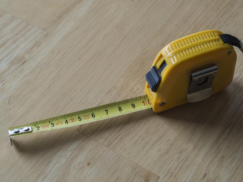 Κίτρινο μέτρο ταινιών μέτρησης που παρουσιάζει δέκα εκατοστόμετρα σε ξύλινο στοκ φωτογραφίες με δικαίωμα ελεύθερης χρήσης