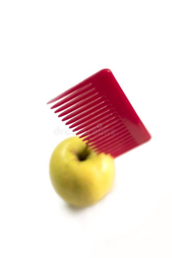 Κίτρινο μήλο και κόκκινη πλαστική χτένα που κολλιούνται σε το στοκ εικόνα