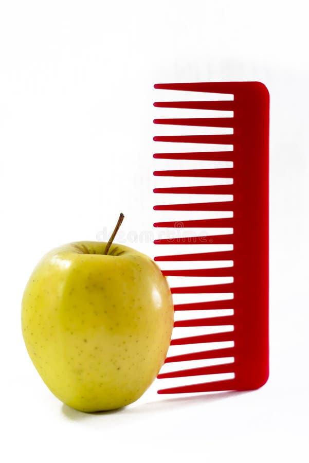 Κίτρινο μήλο και μια κόκκινη πλαστική χτένα που κολλιέται στοκ εικόνα