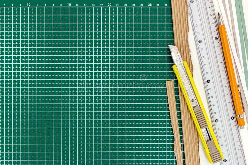 Κίτρινο μαχαίρι κοπτών με τα φύλλα κυβερνητών, μολυβιών και εγγράφου σε πράσινο στοκ φωτογραφία με δικαίωμα ελεύθερης χρήσης