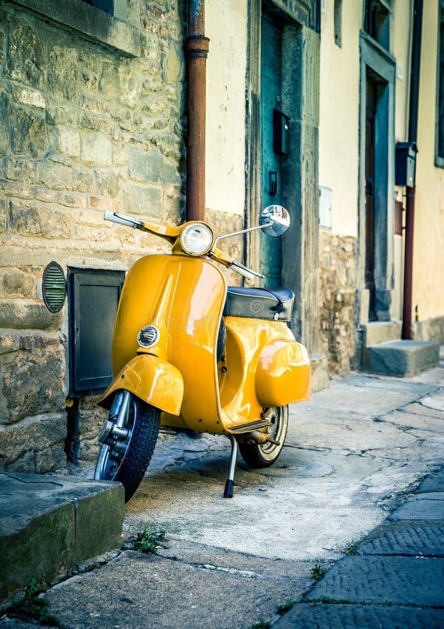 Κίτρινο μηχανικό δίκυκλο στη tuscan πόλη Cortona στοκ εικόνες